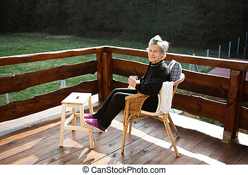 Senior woman on wooden terrace, resting with feet up. -...