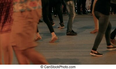 Defocused shot of couples dancing salsa on open air party in...