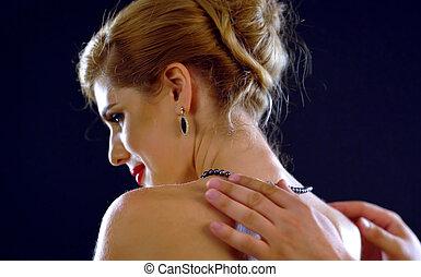 Man helps woman to wear jewelery. Friend male hands puts...