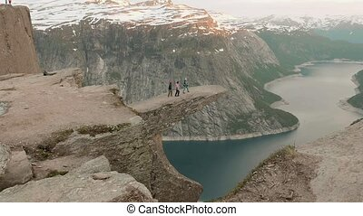 Three friends on the Trolltunga. Norway, sunset - Three...