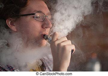 Young man smoking electronic cigarette near window. vaping.