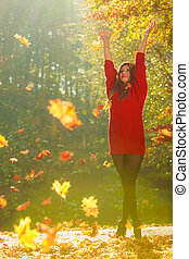 Girl tossing up leaves. Young woman in autumnal forest...