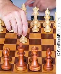 Hand with pawn makes first move on chess Board - The...