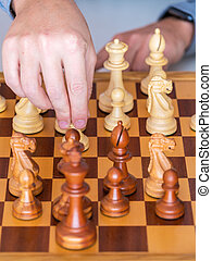Middle game - the hand with pawn makes a move on chess Board...