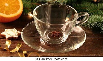 Mulled wine with spices pouring into glass cup