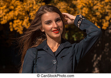 beautiful young girl with red lipstick on lips and black shirt in the Park