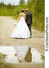 Newly-married couple walks on rural road after a rain
