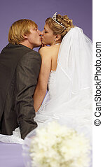 Kissing newlyweds on a purple background