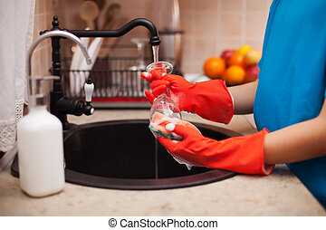 Washing the dishes after a meal - child hands scrubbing a...
