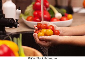 Making a vegetables salad, washing ingredients - cherry tomatoes under the water jet, shallow depth