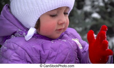pretty young girl shakes snow from her clothes outdoors at winter time
