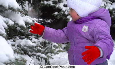 cutie young girl shakes snow from the trees and smiling on camera outdoors