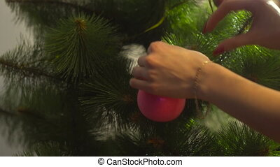 girl decorates the Christmas tree and hang on a branch the pink ball