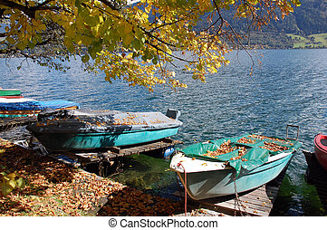 Boats in autumn - Boats covered with leafs on autumn in Zell...