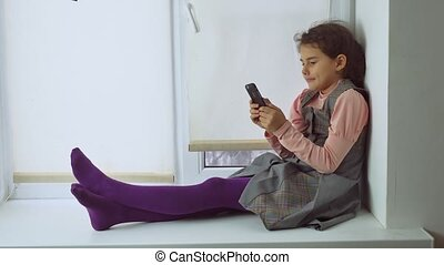 teen girl sitting on a window sill plays the online game for...