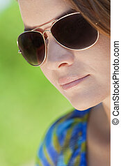 Portrait of a beautiful brunette young woman wearing aviator sunglasses shot outside in sunlight with a natural green background
