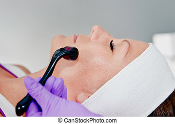 Collagen induction - Treating face with dermaroller