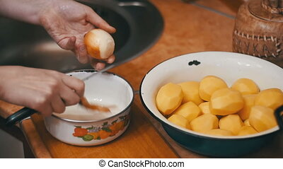Woman's Hands Peeling Potatoes in the Home Kitchen. Slow...