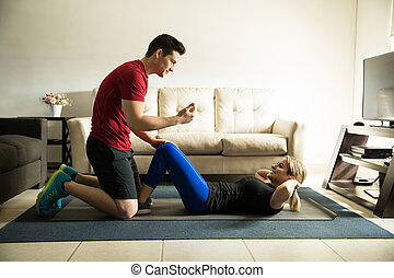 Cute couple exercising together - Profile view of a young...