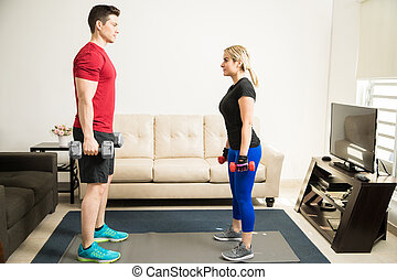 Couple lifting weights at home together - Full length...