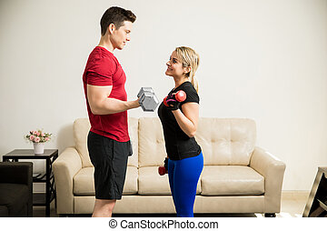 Pretty woman lifting weights with her boyfriend