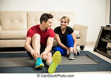 Getting ready for exercising at home - Hispanic young couple...