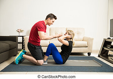 Couple helping each other exercise - Profile view of a young...