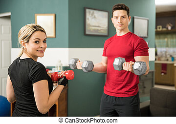 Cute woman lifting weights with her boyfriend - Portrait of...