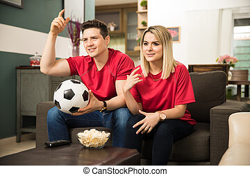Disappointed soccer fans watching a game - Young Latin...