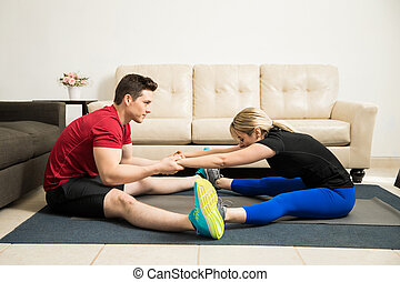 Couple doing stretching exercises together - Young couple...