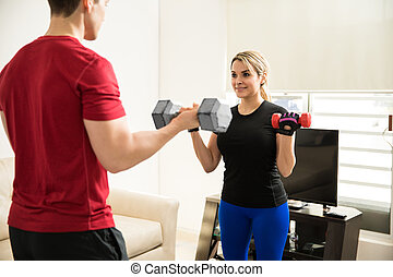 Couple doing bicep curls together - Cute young couple doing...