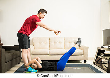 Man helping his girlfriend exercise at home - Profile view...
