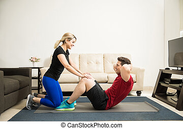 Woman helping her boyfriend exercise - Profile view of a...