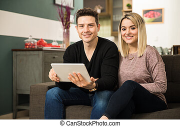 Hispanic young couple using a tablet