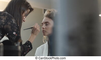 Makeup artist paints the bride's eyes - Makeup artist paints...