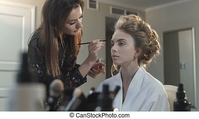 Makeup artist paints the bride's eyes