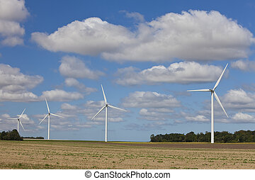 Row of Four Green Energy Wind Turbines In a Field - A farm...