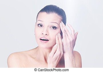 Young woman examining her face and wrinkles that can appear,...