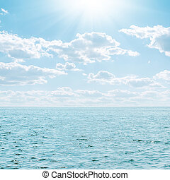 blue sea and sky with clouds and sun