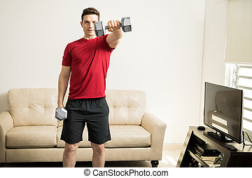 Athletic man lifting weights in the living room - Handsome...
