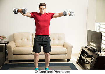 Man working on those shoulders at home - Athletic Hispanic...