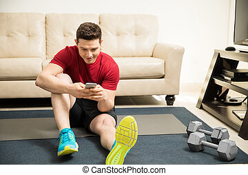Using a smartphone while exercising - Young man taking a...