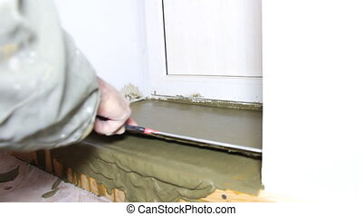 Plasterer smooths the surface with a large spatula