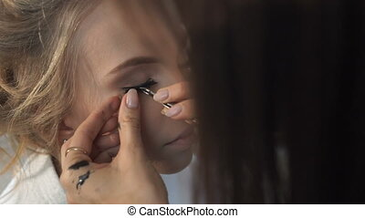 The procedure for eyelash extensions, make-up artist is...
