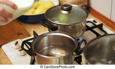 Milk is Poured into a Pan on the Stove in a Home Kitchen....