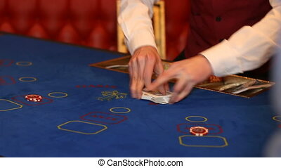 dealer shuffles a deck of cards at casino table - dealer...
