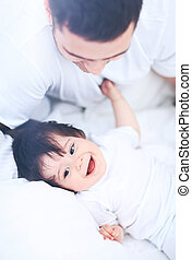 Baby boy lying on bed, next to his father - Father and Son...