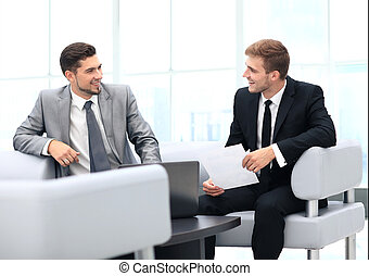 Image of business partners discussing documents and ideas at...