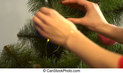 girl decorates a christmas tree with blue ball on branch -...