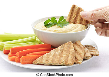 Hand dipping pita in hummus - Hand dipping slice of pita...